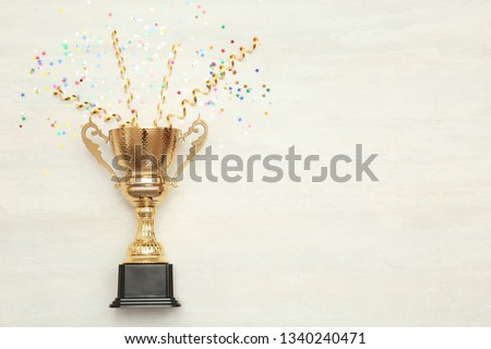 Golden trophy cup and streamers on wooden background, top view with space for text Royalty-Free Stock Photo #1340240471