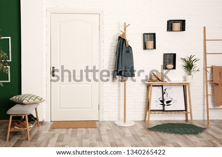 Stylish hallway interior with shoe storage bench, hanger stand and table #1340265422
