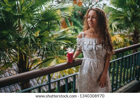 girl on a balcony in the tropics is drinking a drink #1340308970