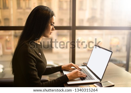Female smart university student learning online via pc laptop computer with empty mock up copy space display background for advertising text message, sitting in modern interior near window in evening