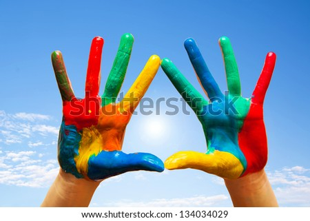 Painted hands, colorful fun. Creative, funny and artistic means happy! Blue sky background