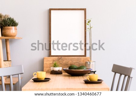 Stylish and sunny interior of kitchen space with small wooden table with mock up photo frame, design cups and avocado. Scandinavian room decor with kitchen accessories and beautiful plants. #1340460677