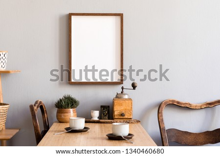 Retro and stylish interior of kitchen space with small wooden table with brown mock up photo frame, design cups and vintage chairs.Scandinavian room decor with kitchen accessories and succulents.