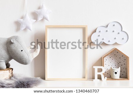 The modern scandinavian newborn baby room with mock up photo frame, wooden toy, plush rhino and clouds. Hanging cotton  white stars. Minimalistic and cozy interior with white walls.Real photo.Template