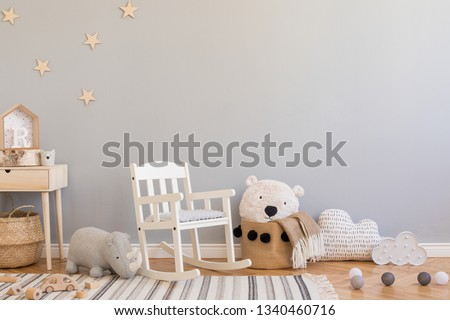 Stylish and modern scandinavian newborn baby interior with toys, children's chair,plush rhino, natural basket with teddy bear and small wooden shelf. Grey background walls with stars pattern. Royalty-Free Stock Photo #1340460716