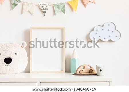Stylish and modern scandinavian newborn baby interior with mock up photo or poster frame on the white shelf. Toys, teddy bear, wooden car and hanging cotton colorful flags and star. Template. Blank. #1340460719