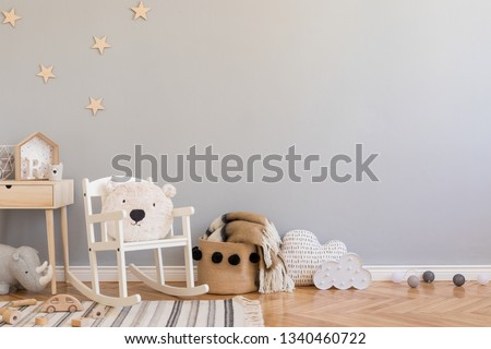 Stylish scandinavian newborn baby room with toys, teddy bear on children's chair, natural basket with blanket. Modern interior with grey background walls, wooden parquet and stars pattern. Real photo. #1340460722