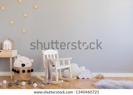 Stylish scandinavian newborn baby room with toys, children's chair, natural basket with teddy bear and small shelf. Modern interior with grey background walls, wooden parquet and stars pattern. #1340460725