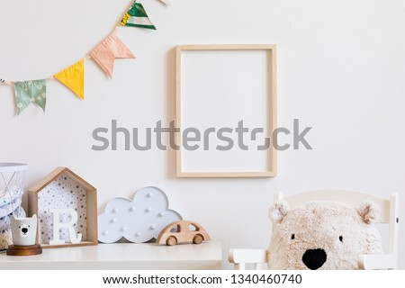 Stylish scandinavian child room with mock up photo poster frame on the white wall. Cute modern interior of nursery with boxes, teddy bear, toys.  wooden accessories and colorful flags. Real photo. Royalty-Free Stock Photo #1340460740