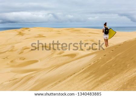 Woman with sandboard Giant sand dunes, Te Paki, Northland, North Island, New Zealand #1340483885