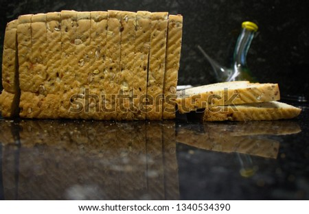 loafs of bread on black table, and a recipient of olive oil on background #1340534390
