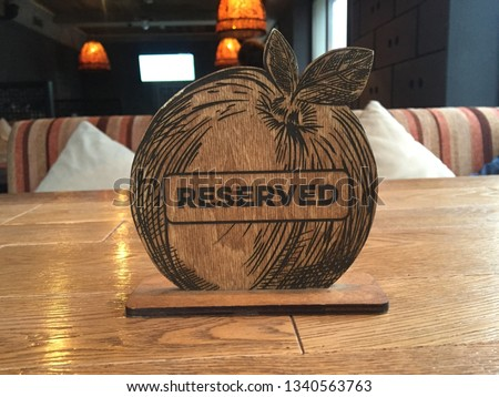 Reserved Table. A tag of reservation placed on the wood table. Reserved logo. Reservation sign. Metal tag with reservation logo. Reserved table in a restaurant. Hungry. Reservation in cafe restaurant  #1340563763