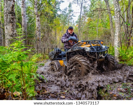 A man rides on ATV through the mud. Riding a quad bike. A man rides an all-terrain vehicle. Riding off-road on an ATV. Outdoor activity. Extreme. Rent a quad bike. #1340573117