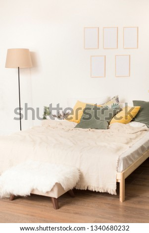 room with a light bed, a floor lamp and a photoframework on a wall. multi-colored pillows, yellow and green color on a bed. #1340680232
