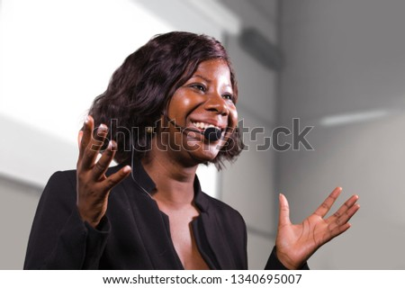 young attractive and confident black African American business woman with headset speaking in auditorium at corporate training event or seminar giving motivation and success coaching conference Royalty-Free Stock Photo #1340695007