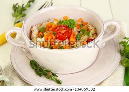 Delicious rice with vegetables and herbs in pot on wooden table close-up #134069582