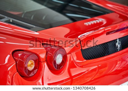 BANGKOK, THAILAND - FEBRUARY 21, 2019: Shiny red Ferrari F430 supercar taillight with reflection on paint. Luxury sports car after ceramic coat. Car detailing & garage concept. Automotive background. #1340708426