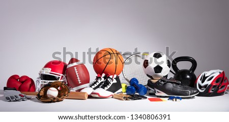 Variety Of Sport Balls And Equipment In Front Of Gray Surface #1340806391