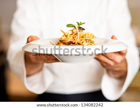 Chef holding mouth watering pasta salad, ready to serve. #134082242