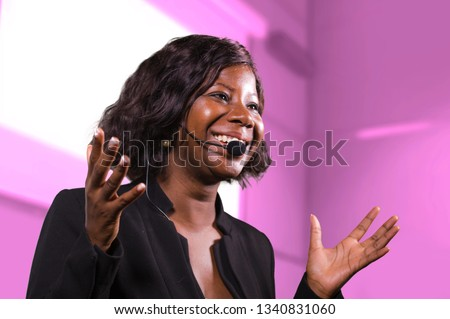 young attractive and successful black afro American business woman with headset speaking in auditorium at corporate training event or seminar giving motivation and success coaching conference #1340831060