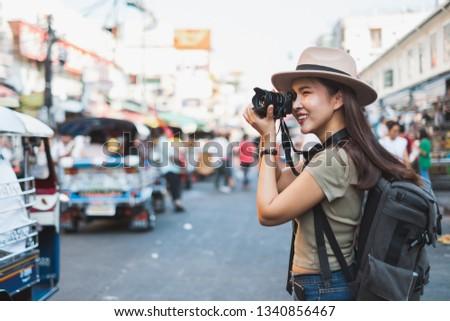 Asian woman tourist backpacker travel and taking photo in Khao San road, Bangkok, Thailand #1340856467