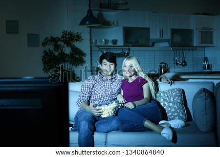 Young couple with bowl of popcorn watching TV on sofa at night #1340864840