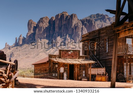 Old Western Wooden Buildings in Goldfield Gold Mine Ghost Town in Youngsberg, Arizona, USA surrounded by cactuses #1340933216