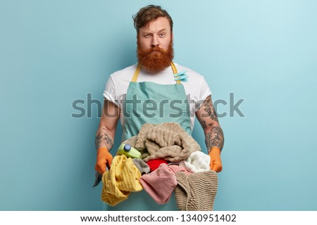 Laundry day concept. Serious bearded red haired Caucasian man busy doing housework, holds basket full of dirty clothes, wears apron with clothespins, protective gloves uses washing detergent #1340951402