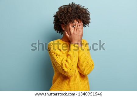 Photo of scared ethnic woman peeks through fingers, hides face, afraids of seeing something terrible, has Afro haircut, wears yellow clothes, isolated over blue wall. Omg, I dont want to see it Royalty-Free Stock Photo #1340951546