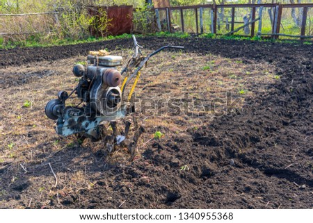 Old vintage dirty motor cultivator on suburban plot. Ploughing ground, land cultivation, soil tillage. Spring work in the garden. Gardening concept #1340955368