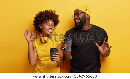 Indoor shot of optimistic brother and sister with dark skin, dance actively to loud music, have holiday, enjoy good sound, drink takeaway coffee, wear black and yellow t shirt, gesture with hands #1340965688