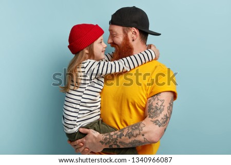 Children, parents, relationship and family concept. Attractive hipster father plays in free time with little daughter, carries on hands, have lovely talk, enjoy togetherness, stand over blue wall. #1340966087