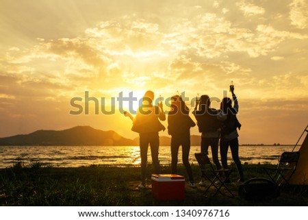 Silhouette Group of women party and dancing with drink bottles enjoy travel camping,trekking in vacation time at sunset. #1340976716