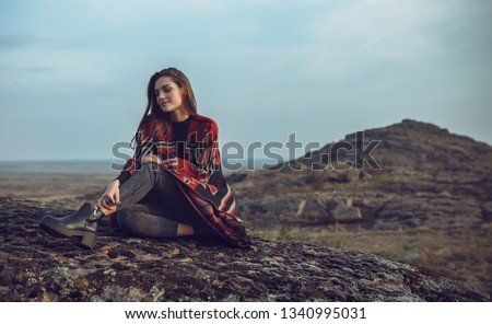 young, beautiful girl sitting on the ground against the backdrop of the mountainous terrain. Plaid draped over the girl's shoulders #1340995031