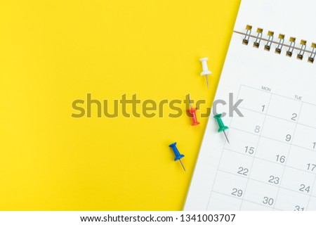 Flat lay or top view of clean white calendar with thumbtack or pushpin on vivid yellow background with copy space using as reminder, vacation plan, business organizer or meeting schedule concept. #1341003707