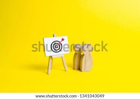 people are standing near the canvas with arrow symbol in the center of the target. Targeting and marketing, advertising. Presentation of information on income and expenses, achievement of goals #1341043049