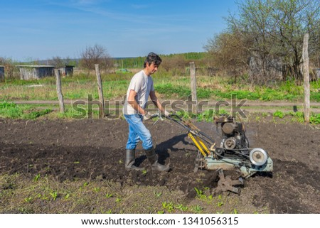 Man in wellingtons with cultivator ploughs ground in sunny day. Land cultivation, soil tillage. Spring work in garden. Gardening concept #1341056315