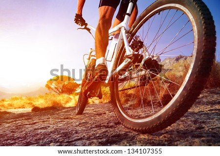 low angle view of cyclist riding mountain bike on rocky trail at sunrise Royalty-Free Stock Photo #134107355