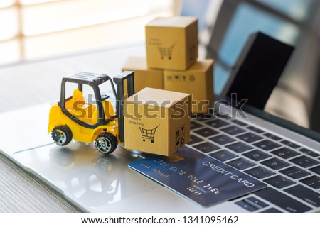 Mini forklift truck load cardboard box with text online shopping and mock up of credit card on laptop keyboard. Logistics and transportation management ideas and Industry business commercial concept. #1341095462