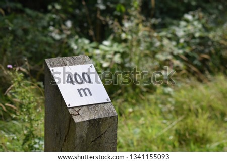 400 meter sign on wooden post with grass and trees in background #1341155093