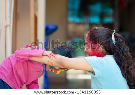 Cute adorable siblings playing with colours during holi festival of colors Indian asian caucasian creative portrait #1341160055