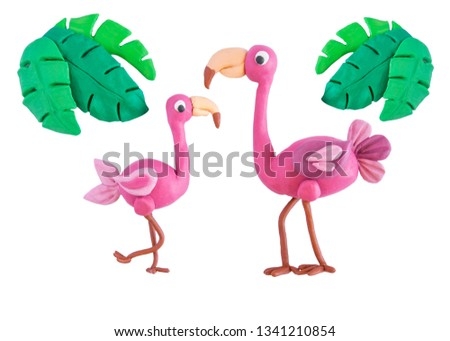 Pink flamingo with palm leaves made of plasticine isolated on white background. Crafts from platinum. Plasticine bird flamingo