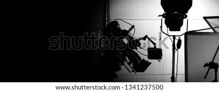 Behind video camera in film or movie production on tripod and professional gear which shooting in location or studio with crew team and prop or set and ready to online live broadcast or tv on air Royalty-Free Stock Photo #1341237500