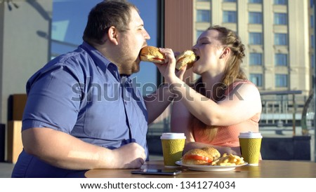 Oversize couple sharing burgers during romantic date outdoors, calories and diet #1341274034