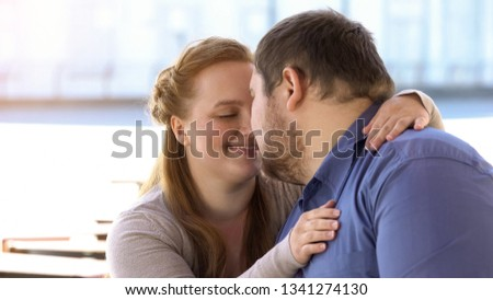 Sweet couple in love nuzzling sitting on city bench, weekend together, closeness #1341274130