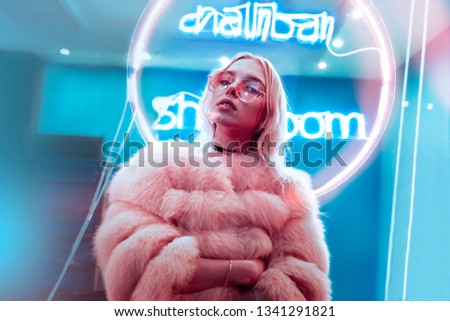 Teen hipster girl in stylish glasses and fur posing near neon sign on street, female teenager fashion model woman with beautiful face looking at camera in city night light glow, back to 80s, portrait #1341291821