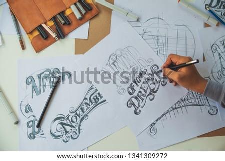 Typography Calligraphy artist designer drawing sketch writes letting spelled pen brush ink paper table artwork.Workplace design studio. #1341309272