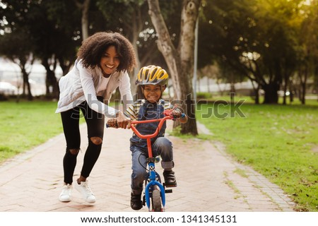 Happy cute boy learn to ride a bike with his mother. Mother teaching son to ride bicycle at park. #1341345131