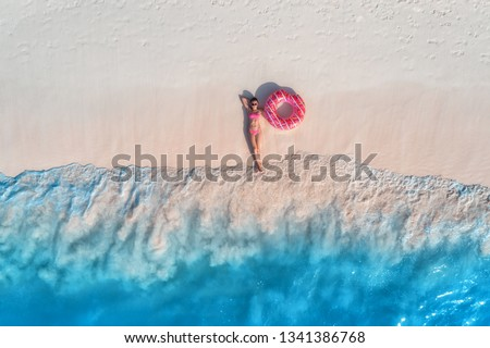 Aerial view of the beautiful young lying woman with pink donut swim ring on the white sandy beach near sea with waves at sunset. Summer holiday. Top view of slim girl, clear azure water. Indian Ocean #1341386768