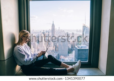 Trendy dressed hipster girl using digital tablet while sitting on hotel window sill with breathtaking scenery view of downtown cityscape. Female working in office with beautiful view of downtown  #1341390077